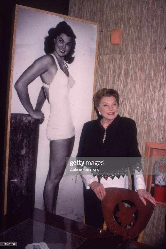 American actor and swimmer Esther Williams standing next to a full-length billboard of herself dressed in a bathing suit at a book party for her autobiography 'Million Dollar Mermaid' held at Tsunami Restaurant in Huntington Beach, California.