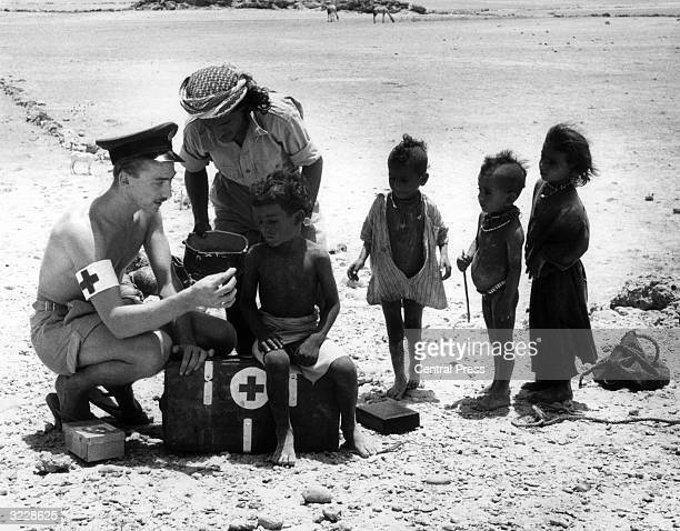 RAF nursing attendant Corporal Cy Thomas treating a group of Bedouin children in the southern Arabian desert