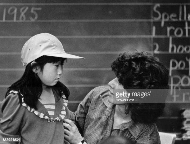 APR 24 1985 APR 25 1985 1st and 2nd grade teacher at Colfax elementary school in Denver Irene Griego check the fit of a cap on student Jeanny Lee...