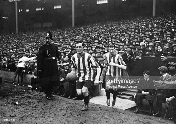 Utley captain of Sheffield United runs on to the pitch with the ball for the FA Cup semifinal replay against Liverpool