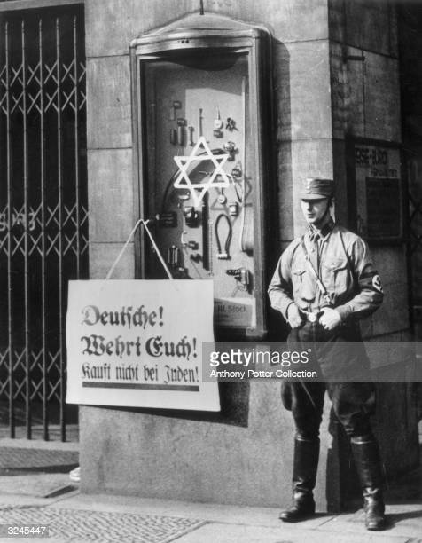 A Nazi Brownshirt soldier stands at window display for a Jewish store in Berlin which bears a sign reads 'Germans Defend yourselves Don't buy from...