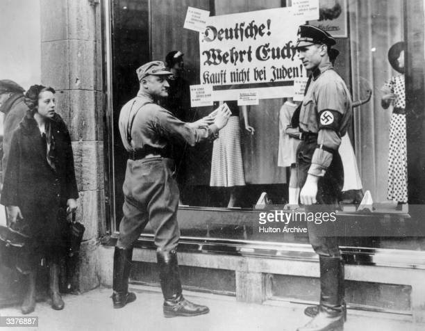 Members of the SA and SS in Berlin pasting a notice onto a Jewish business urging Germans to boycott Jewish shops