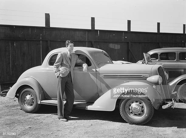 American actor James Stewart leaning against an automobile
