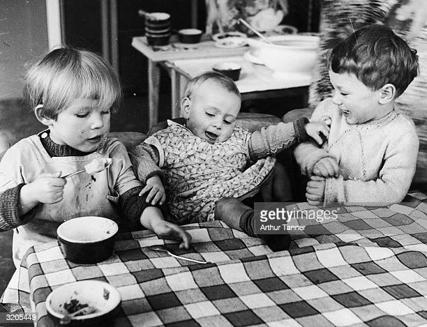 Three children at a nursery school in Bermondsey London the youngest of whom is causing some amusement by putting his feet on the dinner table