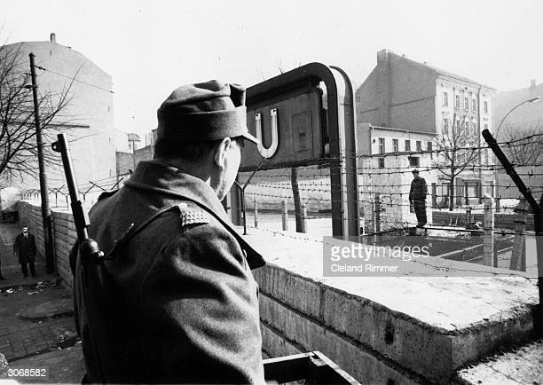 Sentry on the western side of the Berlin wall looks across at his counterpart in the eastern sector