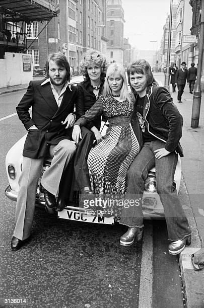 Benny Andersson AnniFrid Lyngstad Agnetha Faltskog and Bjorn Ulvaeus of the Swedish pop group ABBA sitting on the bonnet of a sports car