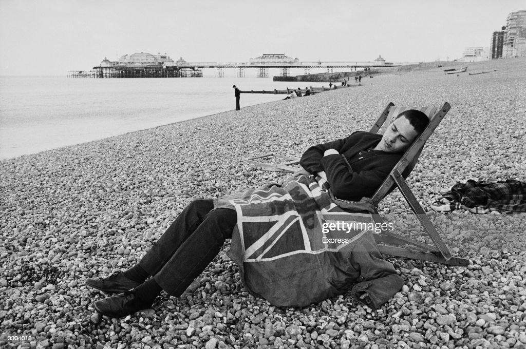 A young Mod asleep on Brighton beach, covered by a Union Jack blanket.