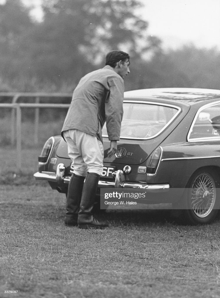 Charles, Prince of Wales closing the boot of an MG sports car at Cowdray Park, Midhurst, Sussex after competing in a polo match.