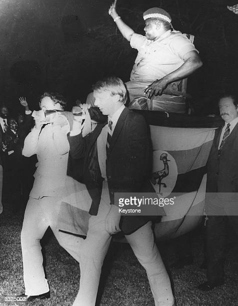 Ugandan soldier and dictator President Idi Amin is carried aloft in a chair by white businessmen at Kampala Uganda