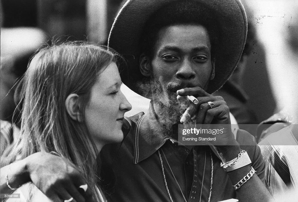 A young couple share a marijuana reefer at Notting Hill Carnival, west London.