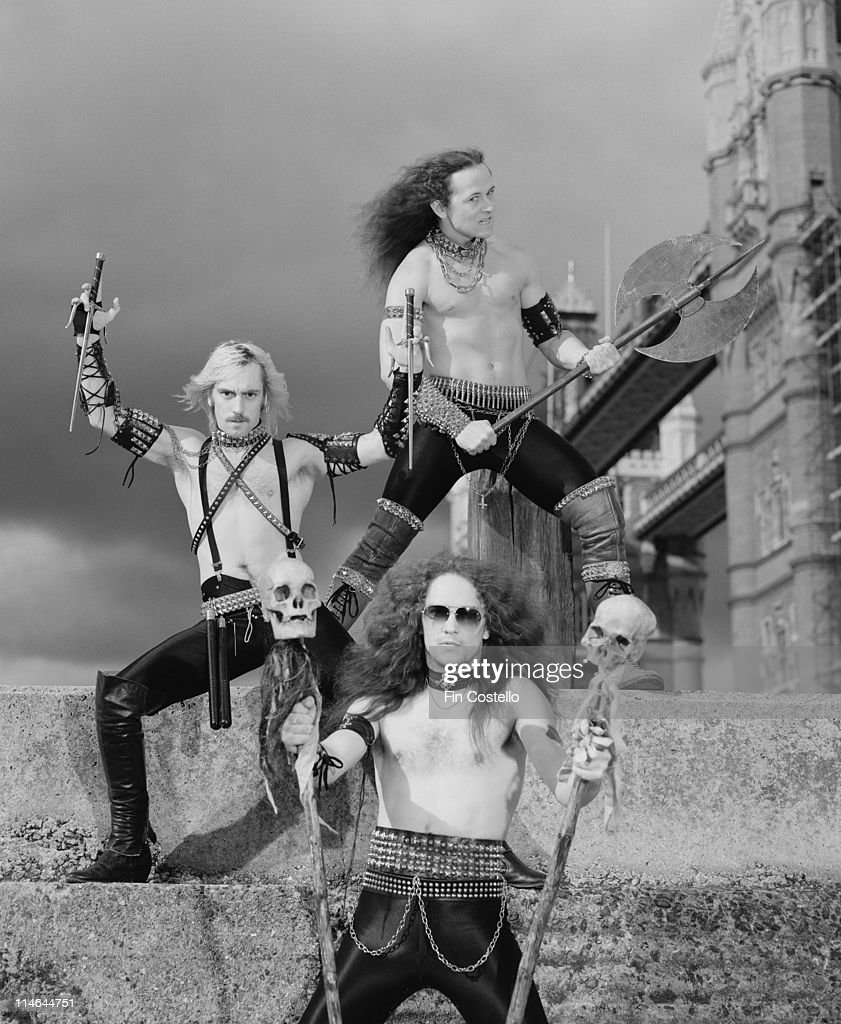 English heavy metal band Venom posed with weapons in front of Tower bridge in London in August 1984. Top to Bottom: bassist Conrad 'Cronos' Lant, guitarist Jeffrey 'Mantas' Dunn and drummer Anthony 'Abaddon' Bray.