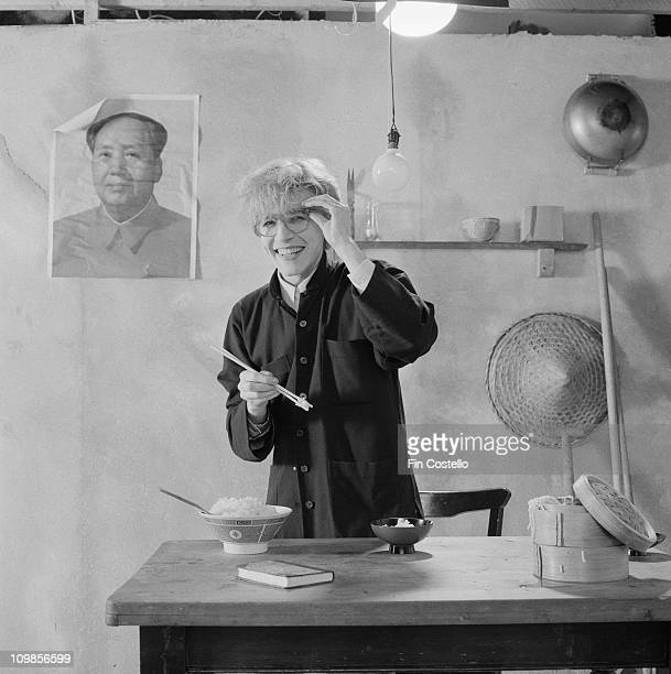 Posed portrait of David Sylvian from Japan holding chopsticks during the Tin Drum album photo session in November 1981 A poster of Chairman Mao hangs...