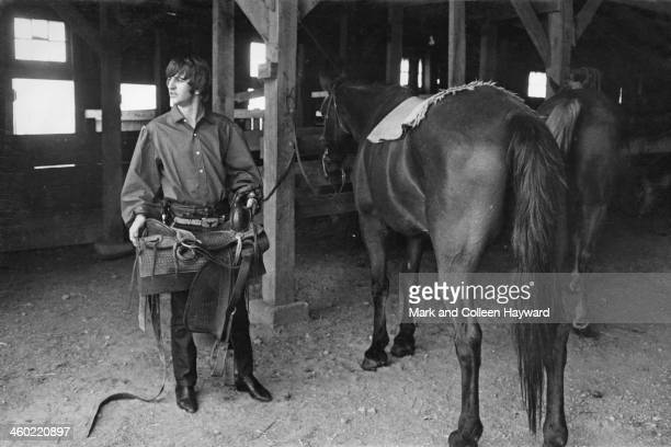 Ringo Starr from the Beatles posed holding a saddle next to a horse in a barn during the band's tour of the United States in August 1964