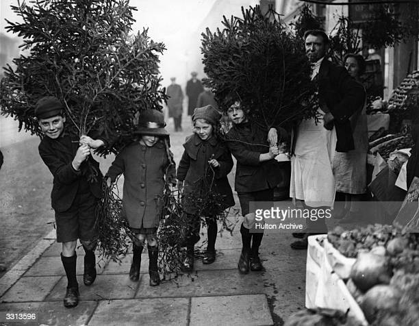 Young children carrying home trees and mistletoe for Christmas