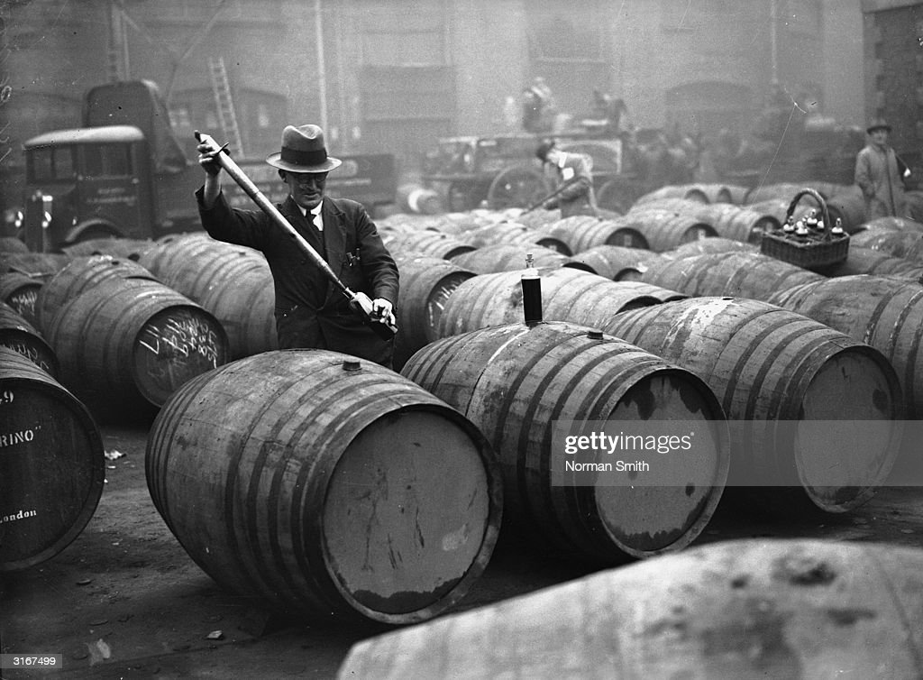 A bond cooper checks the casks of wine being stored by the Port of London Authority in the great vaults at London Docks. Around 1,180,000 gallons of wine are already being kept in the vaults, to cater for the double celebration of Christmas and the upcoming coronation year.