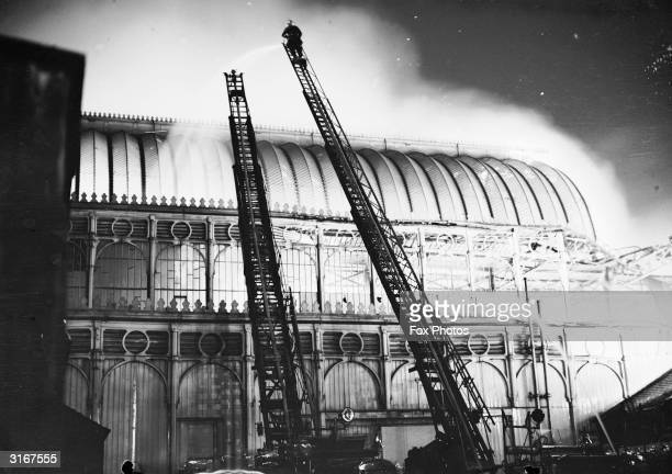 London firemen try to contain the fire which destroyed the Crystal Palace exhibition hall in Sydenham south London