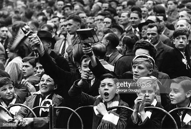 Waving football rattles young football fans at Highbury watch the match between Arsenal and Glasgow Rangers Original Publication Picture Post 5596...