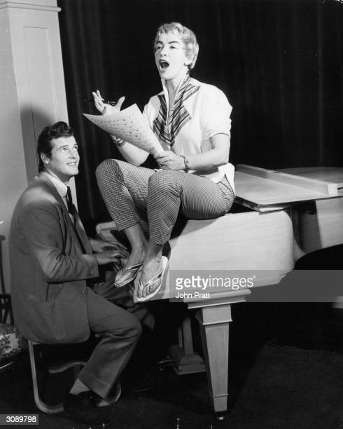 Film star Roger Moore plays the piano for his wife singer Dorothy Squires