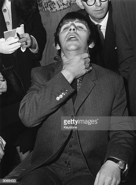 Ringo Starr the Beatles drummer clutches his throat in mock horror as he goes into University College Hospital London to have his tonsils removed