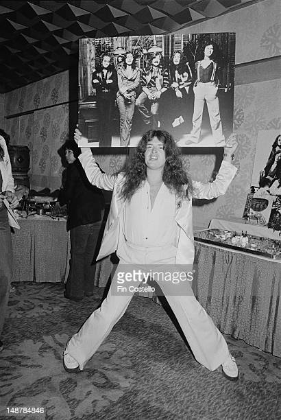 Bass player Glenn Hughes from English rock groups Deep Purple and Trapeze posed holding a poster of Deep Purple at a Warners Record company press...