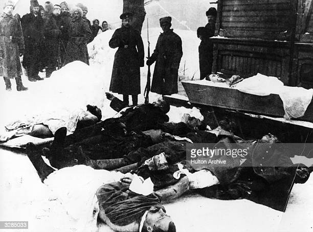 A factionary guards the dead after a day of bloodshed during the Russian Revolution
