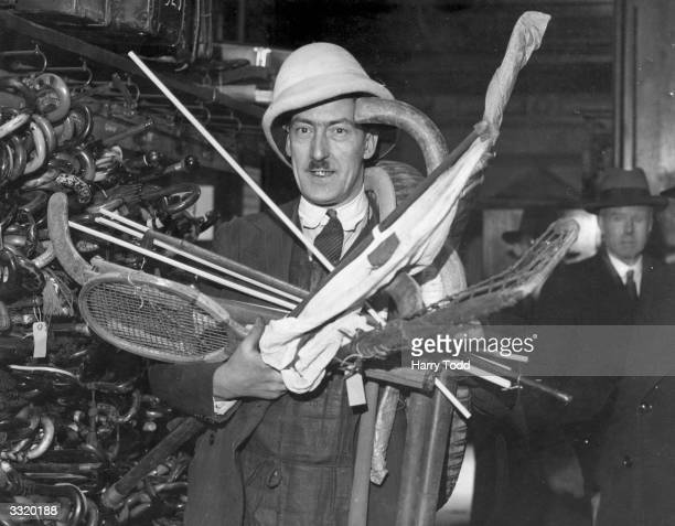 A man wears a pith helmet and holds some of the other items stored at London Transport's lost property office at Baker Street London The items in the...