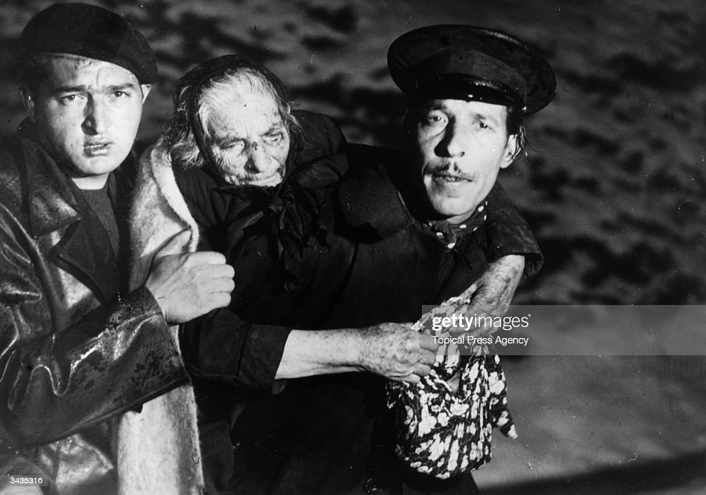 Two members of a rescue party assist an elderly woman fleeing the Spanish Civil War.