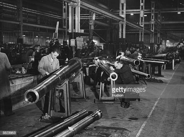 Ordinance workers put the final touches to 37 antiaircraft gun barrels in an assembly shop in the Midlands