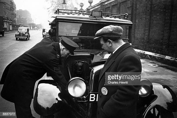London taxi driver Mike Polluck having his cab checked by a police sergeant Each London cab is checked every three months and a 'stop' imposed means...