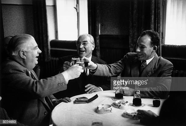 British racing driver Stirling Moss and his father share a toast with Alfred Neubauer team manager of Mercedes Benz Original Publication Picture Post...