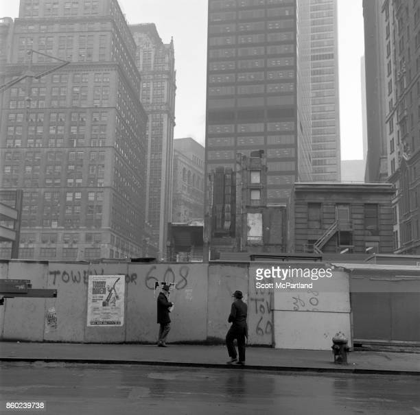 Two men walk by a construction site in Downtown Manhattan on a raw and rainy winter day