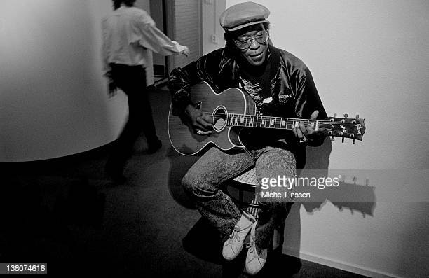 American Blues guitarist and singer Buddy Guy posed playing a guitar backstage in the Netherlands in 1991