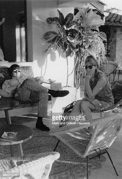 John Lennon from The Beatles relaxes in the shade with his wife Cynthia Lennon on holiday in Port Of Spain Trinidad in January 1966