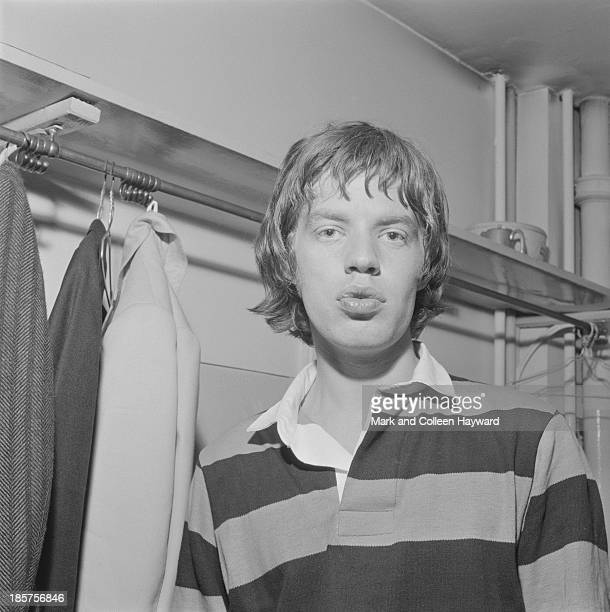 Mick Jagger from The Rolling Stones posed wearing a rugby jersey backstage on tour in Scotland in early 1964