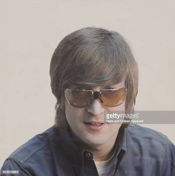 Posed studio session of John Lennon from The Beatles wearing sunglasses in 1965