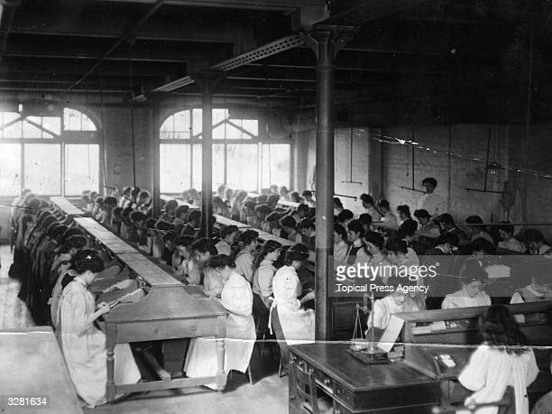 Women rolling tobacco by hand in a factory in Manchester