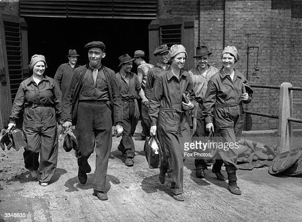 Male and female gas workers leaving the gas works at the end of their shift