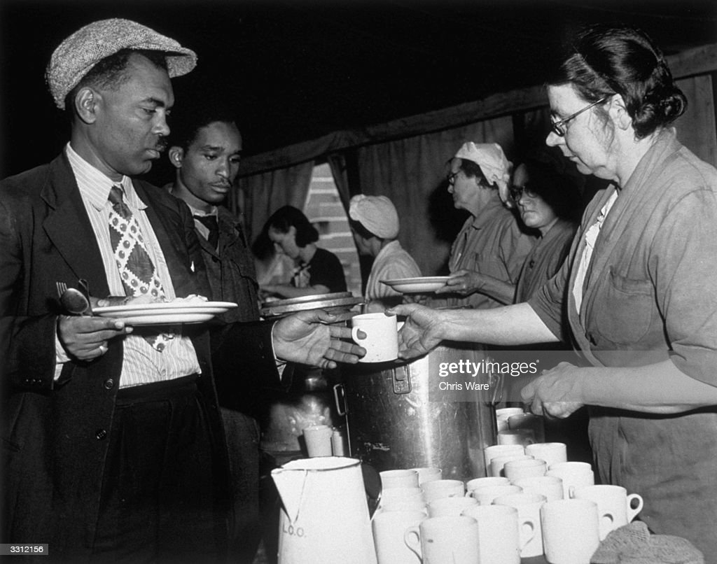 Jamaican immigrants collect a meal from the canteen set up for them at a hostel in the Clapham air raid shelter south London
