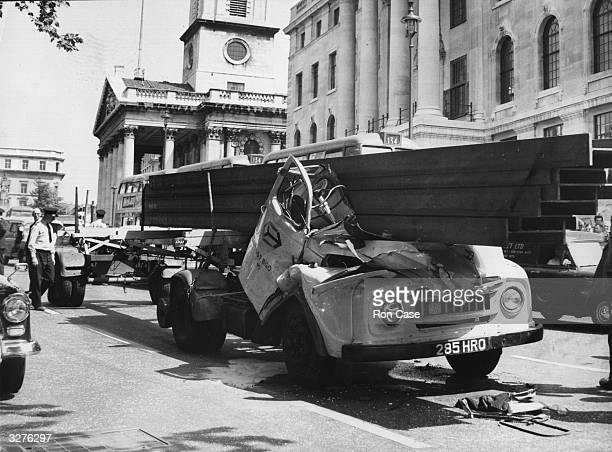 A driver's cab in Trafalgar Square is crushed by the girders it was carrying following an emergency stop Both passengers escaped unhurt