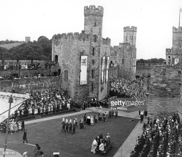 Members of the immediated Royal Family forming a procession at Caernarvon Castle after the Investiture ceremony of Charles Prince of Wales watched by...