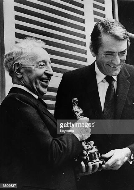 Celebrated pianist Arthur Rubinstein receiving the Hollywood 'Oscar' from Gregory Peck in the Parisian residence of the great musician