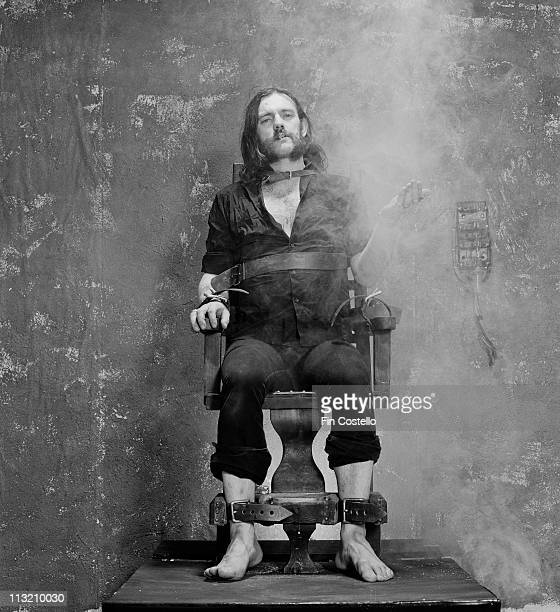 Lemmy Kilmister from Motorhead posed sitting strapped to an Electric Chair prop and smoking a cigarette during the photo session for the 'Killed By...