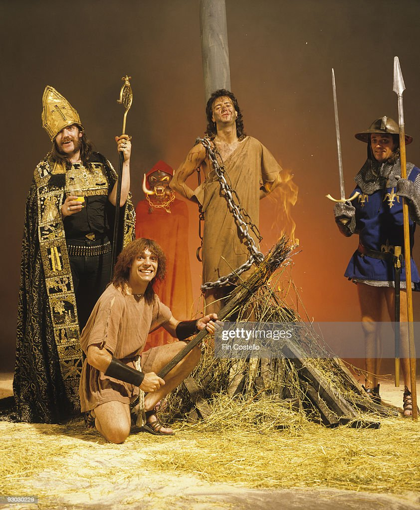 Posed group portrait of Motorhead in mock burning at the stake scene with Lemmy (Ian Kilmister) left in 1984. Left to Right: Lemmy Kilmister, Mick 'Wurzel' Burston, Phil Campbell, Pete Gill.