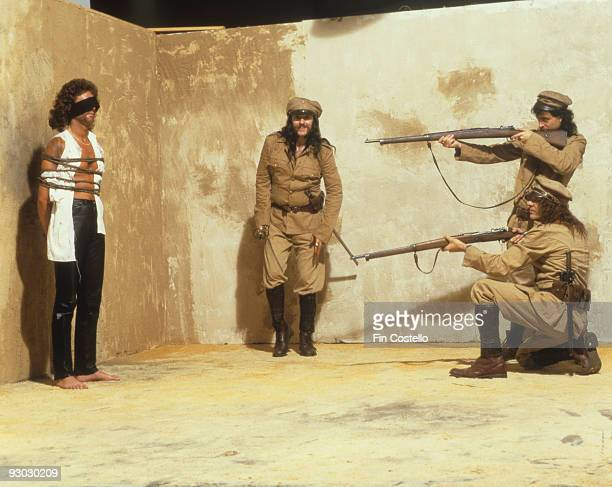 Posed group portrait of Motorhead in mock firing squad scene with Lemmy centre in July 1984 Left to Right Pete Gill Lemmy Phil Campbell and Mick...