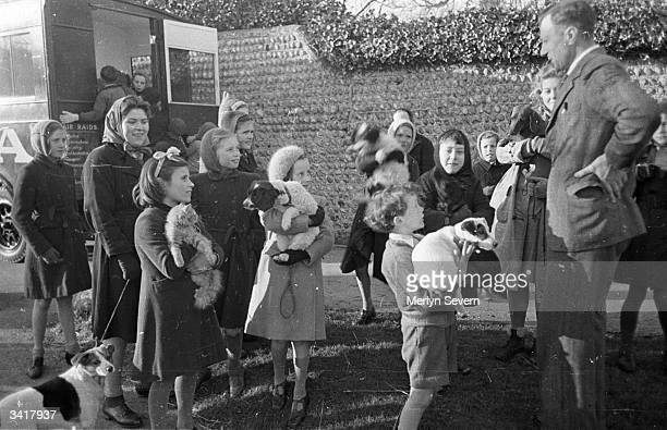 Children and their pets queue outside a PDSA mobile clinic and listen to a staff member who is giving them tips on how to look after their pets...