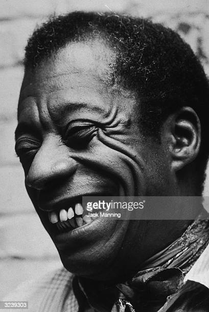 Closeup of American author James Baldwin laughing in his New York City apartment