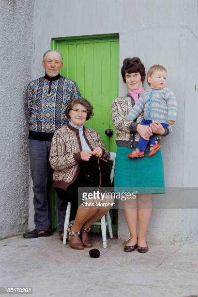 A family of Shetlanders pose wearing Fair Isle jumpers in front of a cottage door on one of the Shetland Islands in June 1970