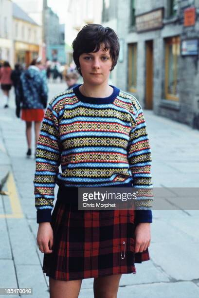 A young woman poses wearing a Fair Isle sweater and kilt in Lerwick Shetland Islands in June 1970
