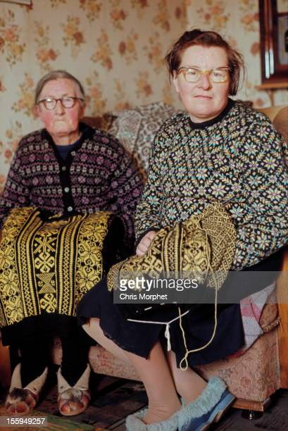 Two elderly women wearing Fair Isle jumpers pose while knitting in the living room of a cottage on one of the Shetland Islands in June 1970