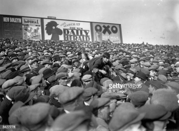A good tempered football crowd at West Ham London pass a young boy over their heads to the front so that he can see the game better
